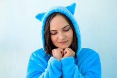 молодая женщина брюнета в пушистых голубых пижамах или костюме кота на голубой пастельной предпосылке стоковое изображение rf