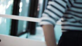 Молодая женщина брюнета в черном платье приходит вверх по белым лестницам акции видеоматериалы