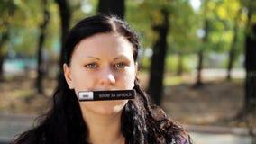 Молодая женщина брюнета с длинными волосами и nameplate на ее взглядах рта на камере сток-видео