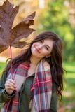 Молодая женщина брюнета с кленовым листом стоковые фотографии rf