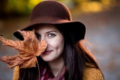 Молодая женщина брюнета с половиной кленового листа покрывая ее сторону стоковое фото rf