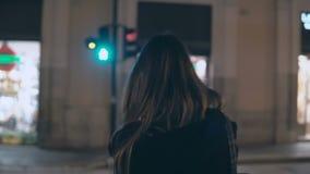 Молодая женщина брюнет пересекая дорогу движения в вечере и идя в центр города самостоятельно, через улицы видеоматериал