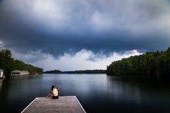 Молодая женщина брюнет сидя на доке около озера наблюдая шторм приходит внутри стоковое изображение