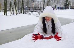 Молодая женщина брюнет устанавливала красные яблока на снеге в сугробе стоковая фотография rf