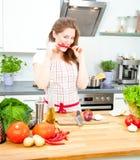 Молодая женщина варя в кухне Здоровая еда - соль овоща стоковые фото