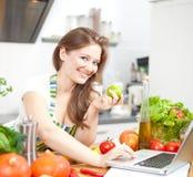 Молодая женщина варя в кухне Здоровая еда - соль овоща стоковое изображение
