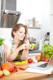 Молодая женщина варя в кухне Здоровая еда - соль овоща стоковые изображения