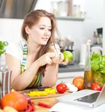 Молодая женщина варя в кухне Здоровая еда - соль овоща стоковые изображения rf