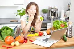 Молодая женщина варя в кухне Здоровая еда - соль овоща стоковая фотография