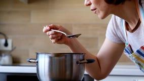 Молодая женщина варя и испытывая слишком солёную еду в кухне акции видеоматериалы
