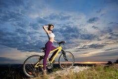 Молодая женщина велосипедиста на велосипеде na górze горы с красивым ландшафтом на заходе солнца Стоковые Изображения RF