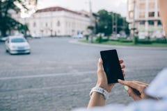 Молодая женщина вида сзади непознаваемая используя умный телефон стоковое фото rf