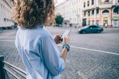 Молодая женщина вида сзади непознаваемая курчавая используя умный телефон стоковое изображение rf