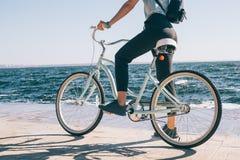 Молодая женщина вида сзади остановила во время велосипеда стоковое изображение