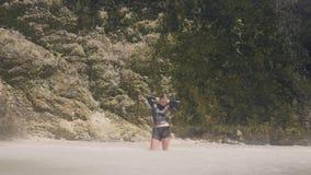 Молодая женщина во влажных одеждах наслаждаясь пропуская водопадом в положении женщины тропического леса счастливом под брызгать  видеоматериал