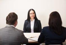 Молодая женщина во время собеседования для приема на работу и членов managemen стоковое изображение