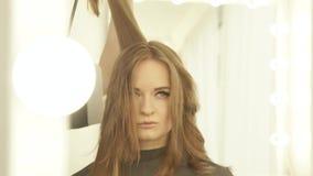 Молодая женщина во время сушить длинные волосы с сушильщиком и зеркалом щетки для волос передним в салоне парикмахерских услуг За акции видеоматериалы