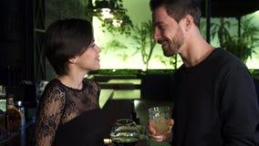 Молодая женщина встречая ее мужского друга на баре видеоматериал