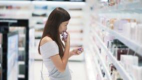 Молодая женщина выбирает духи в косметиках ходит по магазинам и обнюхивает ее, замедленное движение сток-видео