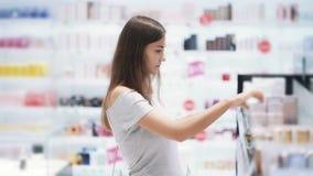 Молодая женщина выбирает духи в косметиках ходит по магазинам, распылила ее, обнюхивает ее, замедленное движение сток-видео