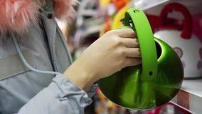 Молодая женщина выбирает зеленый стальной чайник в супермаркете