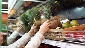 Молодая женщина выбирает и покупает кокосы на супермаркете сток-видео