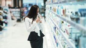 Молодая женщина выбирает косметики в магазине, читает ингредиенты, раскрывает и обнюхивает ее сток-видео