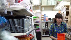 Молодая женщина выбирает малый оранжевый контейнер в супермаркете здания