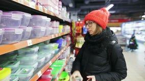 Молодая женщина выбирает пластичную коробку для завтрака в моле Красивая усмехаясь девушка в красной шляпе и стеклах, покупая кух акции видеоматериалы