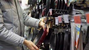 Молодая женщина выбирает сковороду не-ручки в магазине