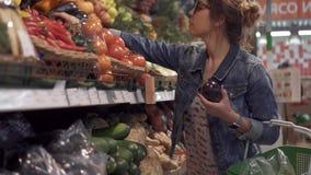 Молодая женщина выбирает vegetable баклажан в большом магазине видеоматериал
