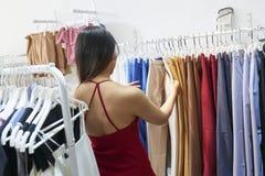 Молодая женщина выбирая брюки стоковая фотография rf