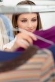 Молодая женщина выбирая рубашку в магазине одежд Стоковая Фотография