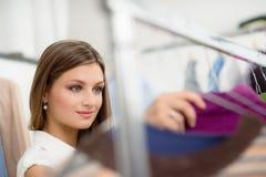 Молодая женщина выбирая рубашку в магазине одежд Стоковые Фото