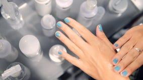 Молодая женщина выбирая сливк заботы кожи руки в супермаркете косметик 4K акции видеоматериалы