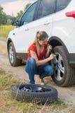 Молодая женщина вывинчивая гайки на колесе ее сломленного автомобиля с плоской покрышкой стоковое фото