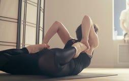 Молодая женщина выполняя йогу-asanas Стоковые Фото