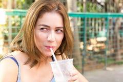 Молодая женщина выстрела в голову смотря к стороне и выпивая ou сока Стоковая Фотография RF