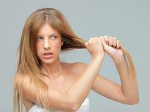 Молодая женщина вытягивая ее damadged волос стоковые изображения