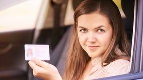 Молодая женщина в автомобиле Инструкция виллиса езды Заем автомобиля Лицензия владением Сидя девушка Посмотрите камеру стоковое фото