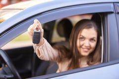 Молодая женщина в автомобиле Инструкция езды Заем автомобиля ключ руки стоковое изображение