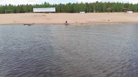 Молодая женщина в бегах платья вдоль пляжа Воздушный всход видеоматериал