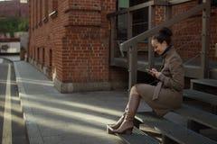 Молодая женщина в бежевом пальто сидит на лестницах стоковая фотография rf