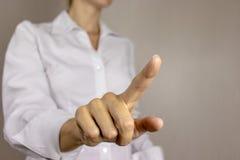 Молодая женщина в белой рубашке указывая, нажимая виртуальную кнопку с ее пальцем владение домашнего ключа принципиальной схемы д стоковая фотография rf
