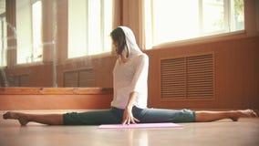 Молодая женщина в белой свободной рубашке сидя на циновке йоги выполняя разделение - делающ ногу протягивая тренировки - танец акции видеоматериалы