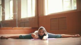 Молодая женщина в белой свободной рубашке сидя на циновке йоги выполняя разделение и полагаясь вперед - студия танца сток-видео