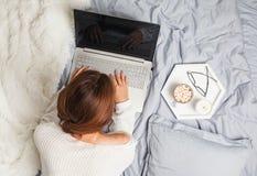 Молодая женщина в белом свитере лежа на кровати и используя компьтер-книжку стоковое фото rf