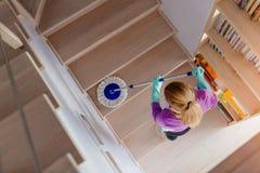 Молодая женщина в белых лестницах чистки рисбермы стоковые фото