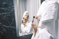 Молодая женщина в белых пальто и полотенце лаборатории на ее голове используя щетку перед зеркалом состава Стоковые Фото