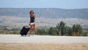 Молодая женщина в белых шортах идет самостоятельно вдоль дороги с чемоданом сток-видео
